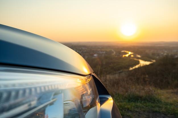 夕暮れ時の現代の車のフロントヘッドライトランプの詳細を閉じます。