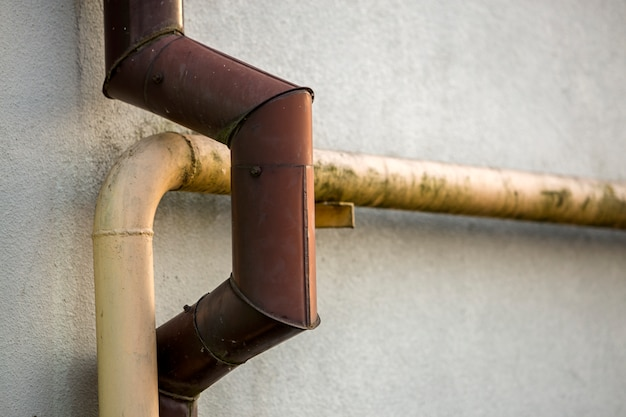 Деталь конца-вверх старых пакостных покрашенных желтых труб дождевой воды природного газа и коричневой сточной канавы