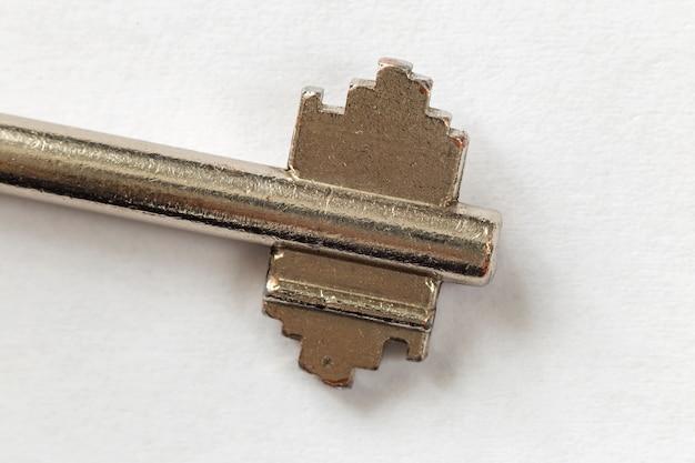흰색 복사 공간 배경에 고립 된 오래 된 잘 사용 된 철강 키의 근접 세부 사항. 안전 및 보안 개념.