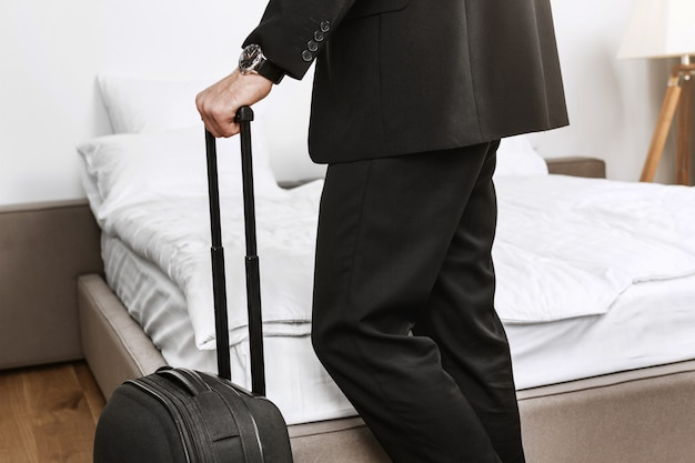ホテルの部屋を離れ、出張から飛行機で家に帰るつもりの手でスーツケースを保持している黒のスーツでスタイリッシュなビジネスマンの詳細を閉じます。