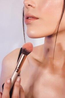 Деталь крупным планом губ красивой девушки с идеальной кожей и кистью для макияжа.