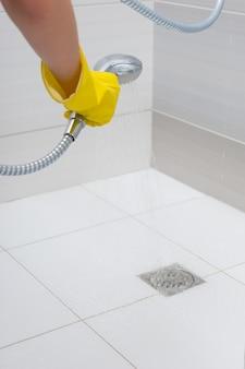シャワー室の床の排水路の周りに水を噴霧する識別できない黄色のゴム手袋の手の詳細をクローズアップ