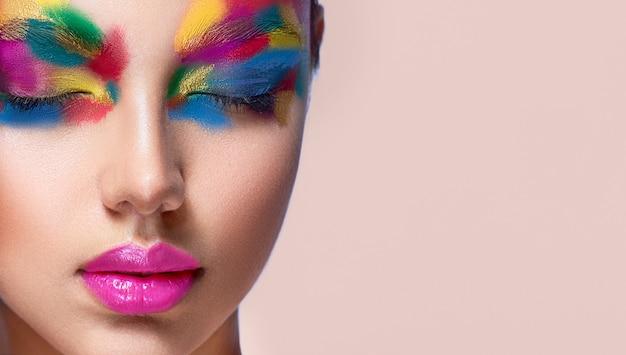 目を閉じて女性の顔の詳細をクローズアップ色合いのパレットで覆われたフェイサー芸術的なメイクアップ
