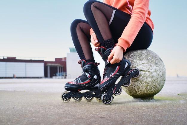 インラインスケートの若い女性の手のクローズアップの詳細