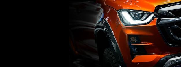 Крупным планом деталь на одной из светодиодных фар оранжевого пикапа, свободное место слева для текста