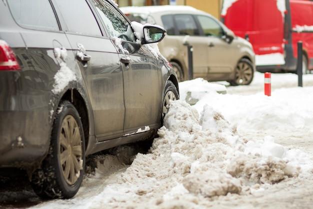 흐리게 겨울 날 배경에 주차장에 깊은 눈에 주차 된 자동차의 근접 세부 후면 부분. 교통, 도시 생활 및 주차 문제 개념.