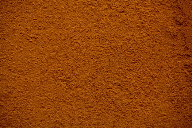 Close up detail of the texture of a painted brown wall with rough finish to the plaster in a full frame view.