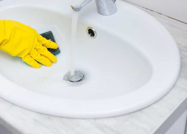 Close up detail view on hand covered with yellow rubber glove wiping down sink bowl with blue sponge and running water