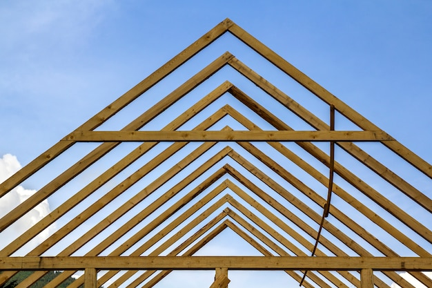 Close-up detail of wooden high steep roof framing under construction. timber frame of natural materials against bright sky. professional building and reconstruction concept.