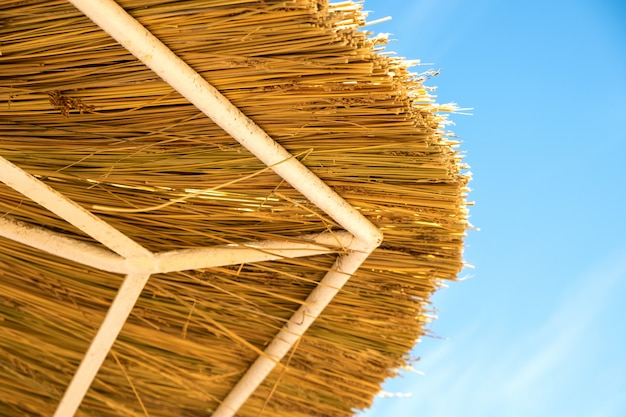 Close up detail of yellow straw roof against blue sky.