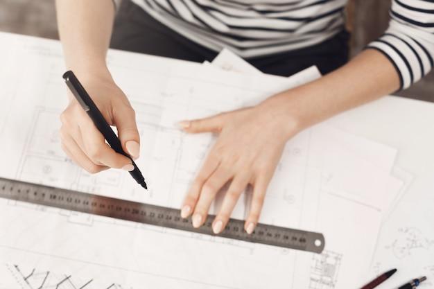 Primo piano dettagliato di giovane ragazza ingegnere di successo in cima a strisce e jeans neri, facendo lavoro a casa, lavorando su un nuovo progetto con la mano e la pistola