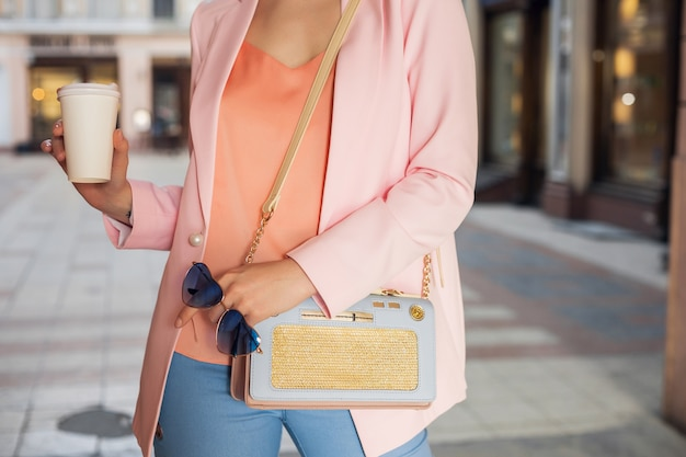 Chiudere i dettagli degli accessori della donna in abbigliamento elegante che cammina in strada tenendo occhiali da sole, borsetta, vestito con giacca rosa, bere caffè, tendenza moda primavera estate