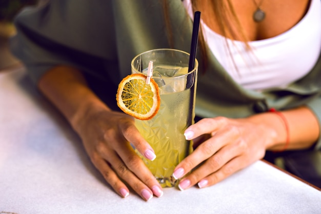 Chiuda sull'immagine dei dettagli della donna che tiene un cocktail fresco e gustoso di limonata, belle mani con french manicure, vestiti alla moda casual, colori tonica.