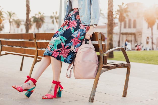 Close up details of legs in pink sandals of stylish woman walking in city street in printed colorful skirt, holding pink leather backpack