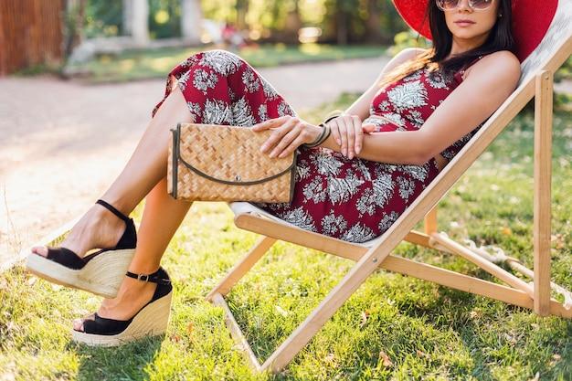Close up dettagli gambe che indossano zeppe sandalo scarpe, calzature. elegante bella donna seduta sulla sedia a sdraio in abito stile tropicale, tendenza della moda estiva, che tiene la borsa di paglia.