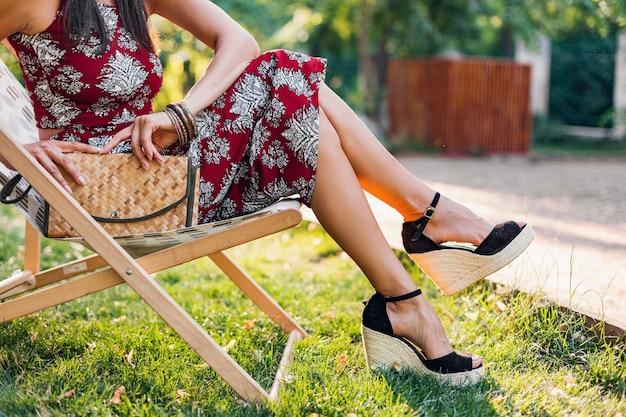 Chiudere le gambe di dettagli che indossano sandali con zeppe, calzature, elegante bella donna seduta sulla sedia a sdraio in abito in stile tropicale, tendenza della moda estiva, borsa di paglia, accessori, vacanze