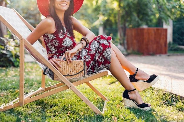 ウェッジサンダルの靴、靴、トロピカルスタイルの衣装でデッキチェアに座っているスタイリッシュな美しい女性、夏のファッショントレンド、わらのハンドバッグ、アクセサリー、休暇を身に着けている足の詳細を閉じる