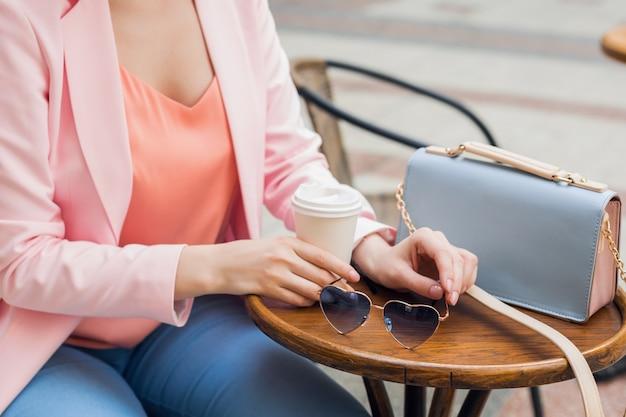 カフェ、サングラス、ハンドバッグ、ピンクとブルーの色、春夏のファッショントレンド、エレガントなスタイルで一人で座っているスタイリッシュな女性のアクセサリーの詳細をクローズアップ