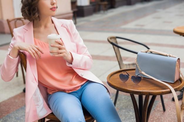 Закройте детали аксессуаров стильной женщины, сидящей в кафе, пьющего кофе, солнцезащитных очков, сумочки, тенденции моды весна-лето, элегантного стиля