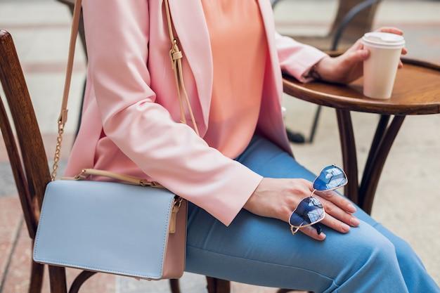 Закройте детали аксессуаров стильной женщины, сидящей в кафе, солнцезащитных очков, сумочки, розового и синего цветов, весенне-летней модной тенденции, элегантного стиля, пьющего кофе