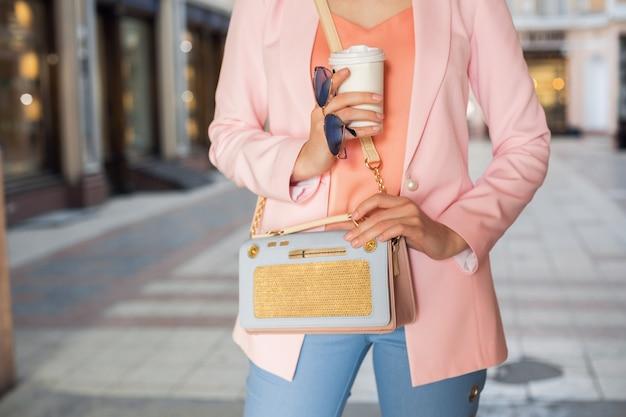Закройте детали аксессуаров женщины в стильной одежде, прогулки по улице, солнцезащитные очки, сумочку, розовую куртку, модные цвета, модную тенденцию весны-лета, элегантный стиль, пьющий кофе