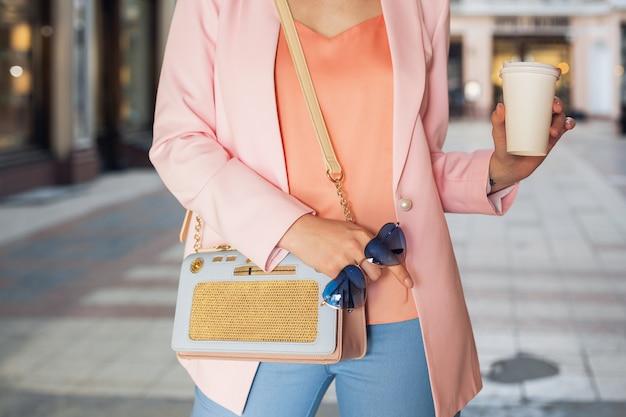 スタイリッシュなアパレル、通りを歩く、サングラス、ハンドバッグ、ピンクのジャケット、流行色、春夏のファッショントレンド、エレガントなスタイル、コーヒーを飲む女性のアクセサリーの詳細をクローズアップ