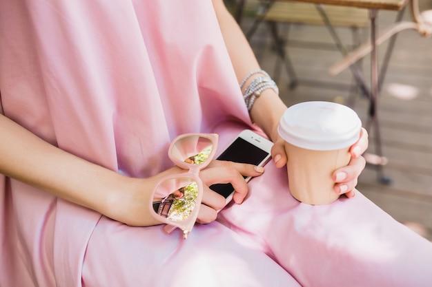 Закройте детали рук женщины, сидящей в кафе в летнем модном наряде, хипстерском стиле, розовом хлопковом платье, солнцезащитных очках, пить кофе, стильных аксессуарах, расслабляющей, модной одежде