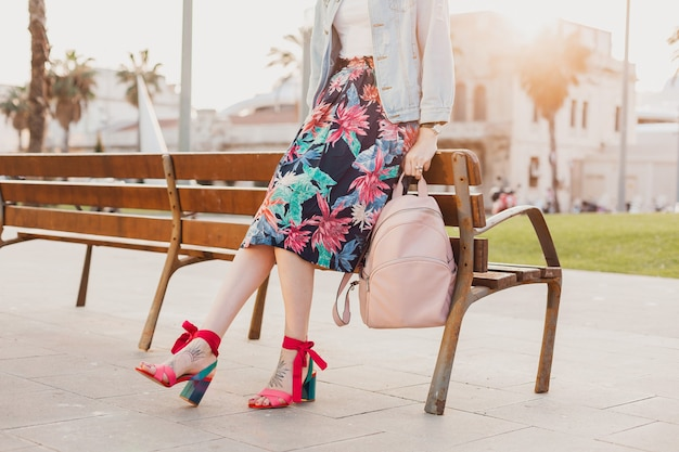 印刷されたカラフルなスカートの街を歩いて、ピンクの革のバックパック、夏のスタイルの靴のトレンドを保持しているスタイリッシュな女性のピンクのサンダルの足の詳細を閉じる