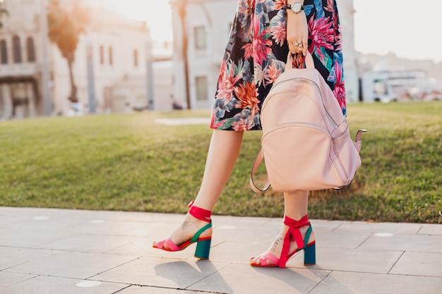 분홍색 가죽 가방, 여름 스타일의 신발 트렌드를 들고 인쇄 된 화려한 치마에 도시 거리를 걷는 세련된 여성의 분홍색 샌들에있는 다리의 세부 정보를 닫습니다.
