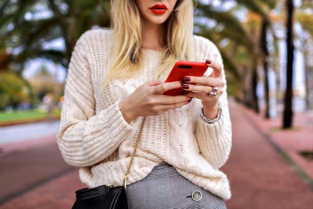 通りでポーズをとる女性の詳細を閉じて、彼女のスマートフォン、赤い唇、居心地の良いトレンディな白いセーター、ファッションをタップします。