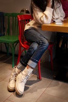 Крупным планом детали женской модной повседневной одежды. ноги в джинсовых брюках и высокие кожаные ботильоны.