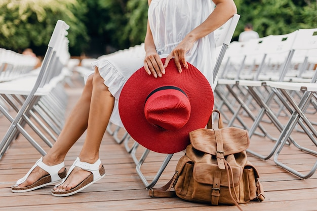 Close-up details of woman in white dress, red hat sitting in summer open air theatre on chair alone, spring street style fashion trend, accessories, traveling with backpack, skinny legs in sandals