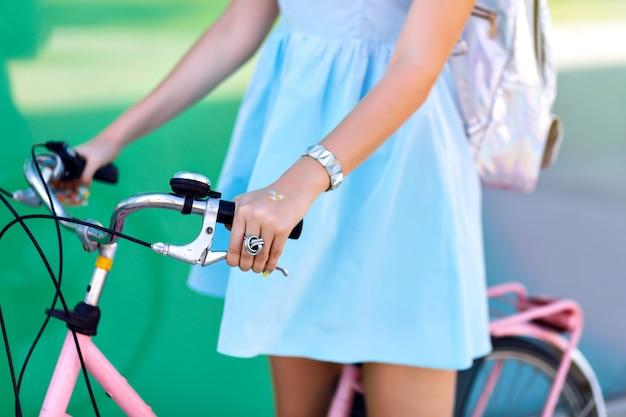 Close up dettagli giovane donna in sella a bici vintage per strada, vestito carino, viaggio hipster umore
