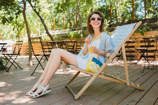 Close up details of young woman sitting in deck chair in summer fashion outfit, white dress, blue cape, yellow purse, drinking lemonade, stylish accessories, long skinny legs in sandals