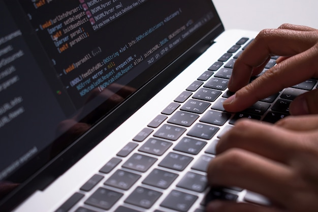 Close up. the developer's hand is creating code on a computer monitor on a white desk.