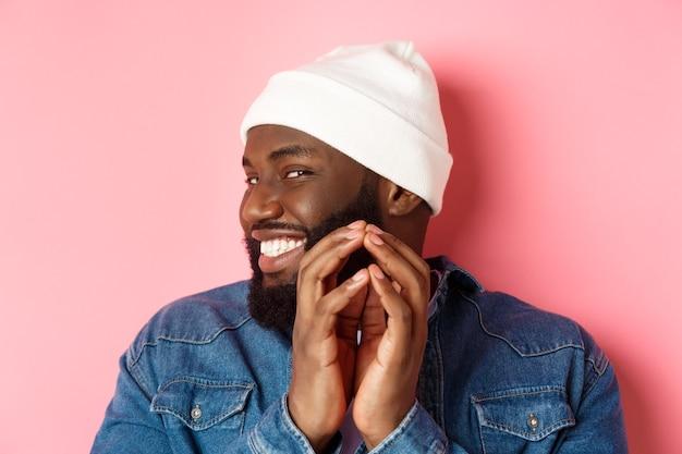 Primo piano del subdolo modello maschio afroamericano che ha un'idea, intriga qualcosa, dita del campanile e sorride sornione, in piedi su sfondo rosa.