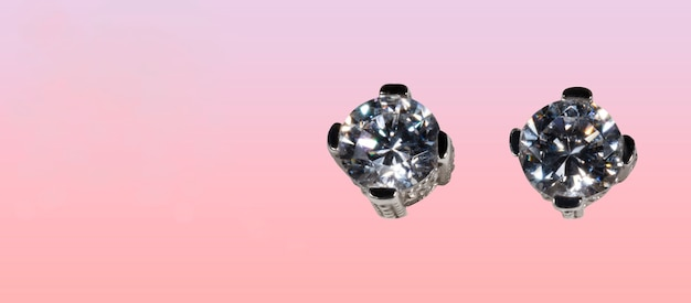Close up of diamond earrings on a pink background space for your text