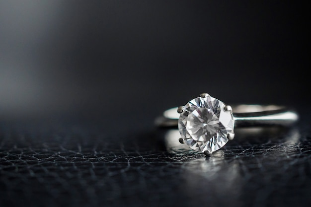 Close up diamond ring jewelry on black leather