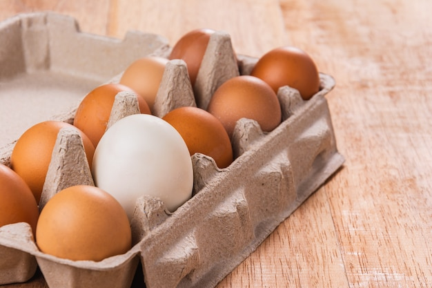 Close-up of different eggs in brown tray on wooden table
