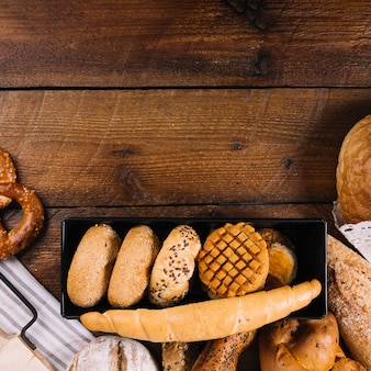 Close-up of different fresh baked bread on wooden table