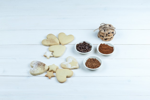 Close-up different types of cookies with coffee beans, instant coffee, cacao on white wooden board background. horizontal