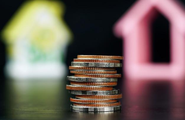 ぼやけた家のモデルで黒い背景に積み上げられたさまざまな種類のコインをクローズアップお金を節約