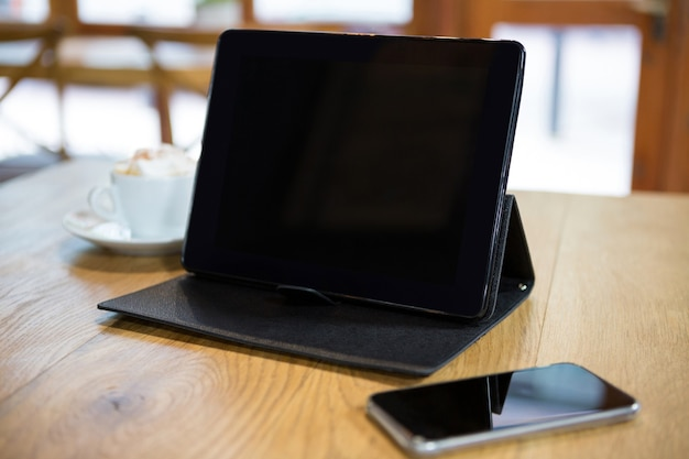 Close-up of digital tablet and smart phone on wooden table in cafe