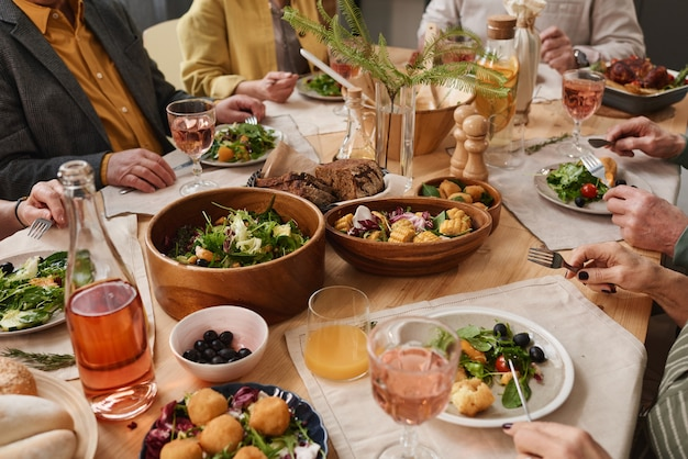 Close-up of dining table with food and drinks and people sitting at the table and eating