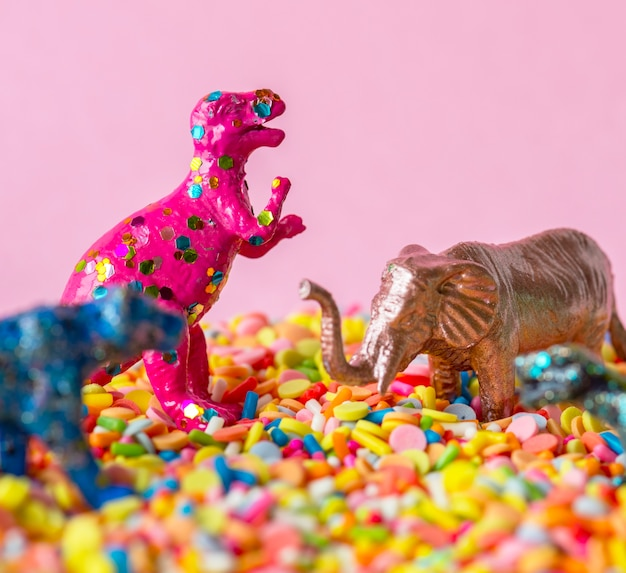Close up of dinosaurs and animal figure toys on sweet candy sprinkles