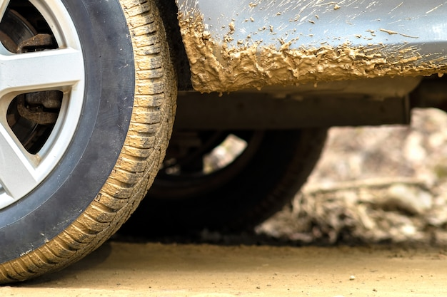 Close up of dirty car wheel with rubber tire covered with yellow mud.