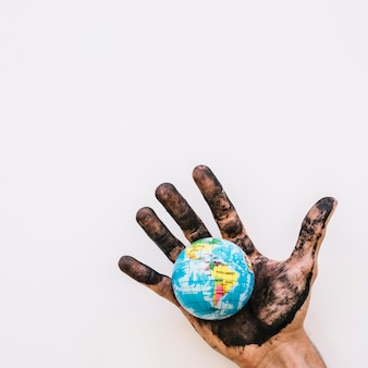 Close-up of dirty human hand with globe over white surface