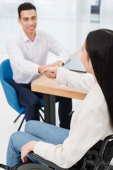 Primo piano di una donna disabile che stringe le mani con il suo uomo d'affari sorridente