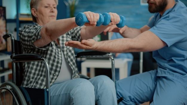 Close up of disabled woman using dumbbells for recovery