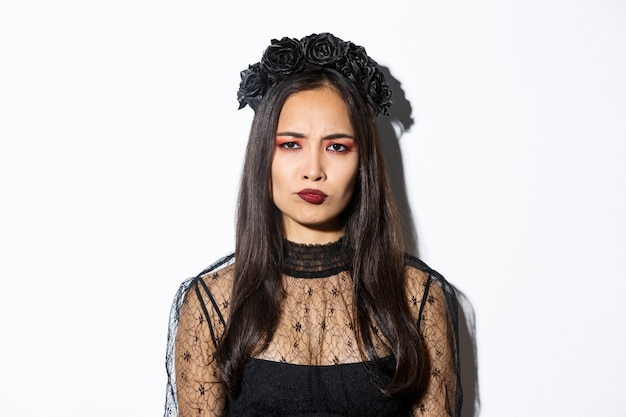 Close-up of disappointed grimacing girl in witch costume looking displeased, frowning upset, standing over white background.